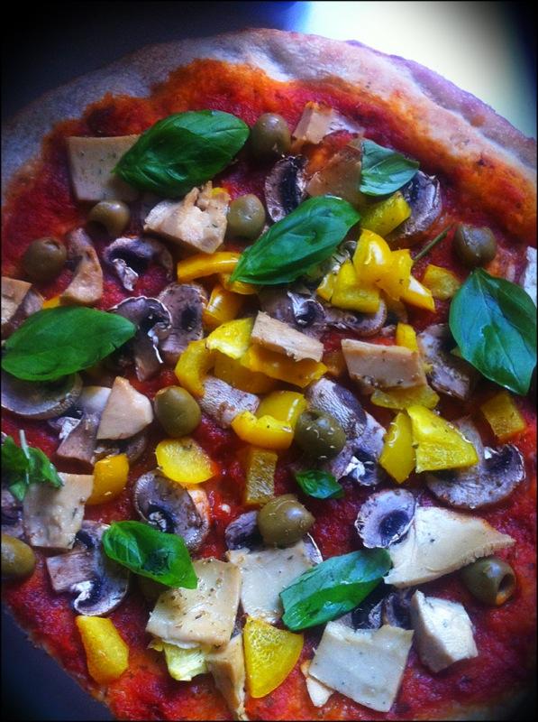 Pizza vegan maison avec poivrons jaunes, champignons, olives, fromage végétal - faut bien le terminer et basilic.
