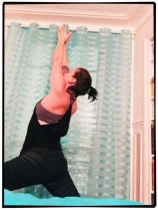 Pratique de yoga enfermée dans la chambre avec iPad posé sur le lit pour photos à l'arrache. Du grand reportage photo.